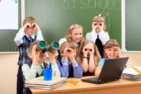 Happy schoolchildren at a classroom looking through binoculars. Education. photo