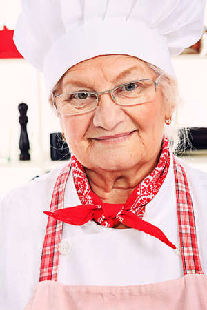 Portrait of a senior woman chef cook in the kitchen. photo