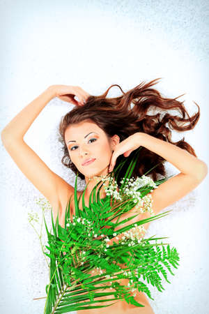 Beautiful young woman lying among fresh green leaves. Isolated over white background photo
