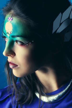 Portrait of a beautiful young woman with fantasy makeup. Dark background. photo