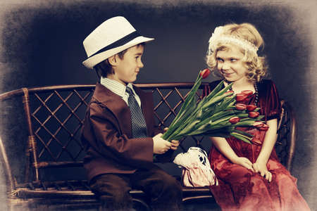 Cute little boy is giving bouquet of tulips to the charming little lady. Retro style. photo