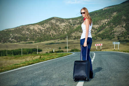 Attractive young woman hitchhiking along a road. photo