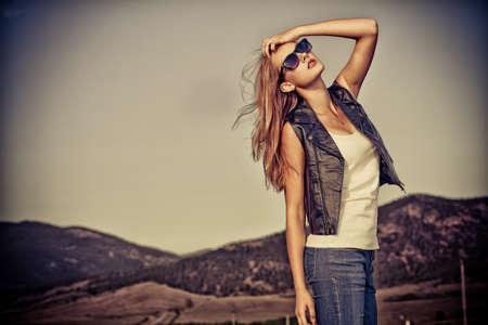 moda ropa: Joven y bella mujer posando en un camino sobre el paisaje pintoresco.