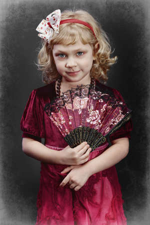 Portrait of a charming little girl with a fan. Vintage style. photo