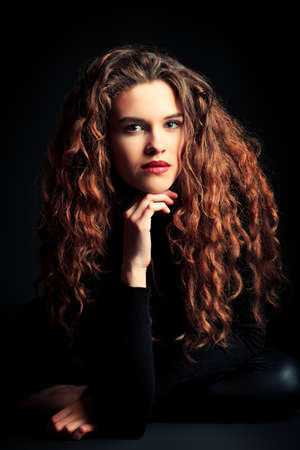 attractive gorgeous: Portrait of a charming fashion model with beautiful curly hair. Over black background.