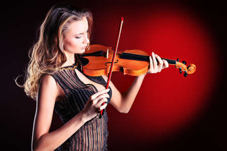 fiddle: Elegant  young woman playing her violin with expression.