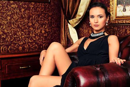 donna ricca: Bella giovane donna in un interno classico di lusso.
