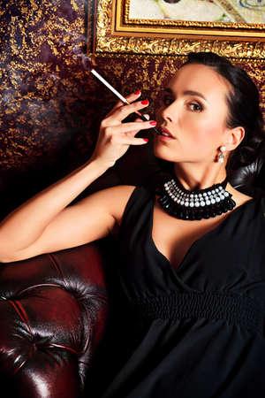 sexy girl smoking: Beautiful young woman in a  luxurious classic interior.