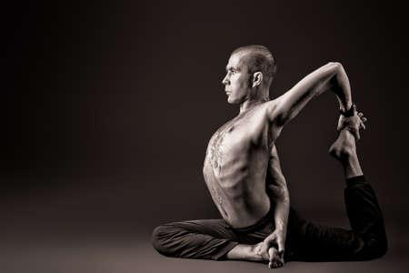 растягивание: Красивый мужчина показывает различные упражнения йоги на черном фоне. Фото со стока