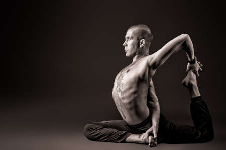 Handsome man shows different yoga exercises over black background. photo
