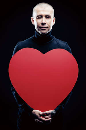 Portrait of a handsome man holding red heart over black background. Valentine day. photo