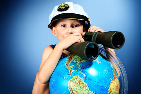 human geography: Little sailor boy sitting with the globe and binoculars. Stock Photo