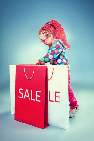 Portrait of a cute little girl with modern red braids standing with shopping bags. photo