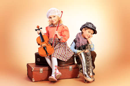 itinerant: Cute little boy with his old saxophone is sitting on a suitcase with charming little lady violinist. Retro style.