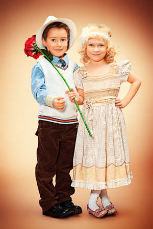 Cute little boy gentleman standing with the charming little lady. Retro style. photo