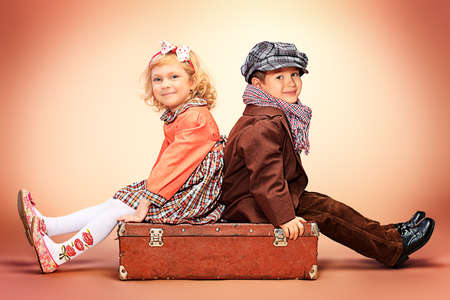 vintage children: Cute little boy is sitting on the old suitcase with charming little lady. Retro style. Stock Photo