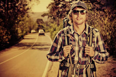 Young man tourist hitchhiking along a road. photo