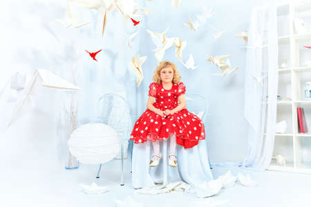 Cute little girl sitting in a white room surrounded with paper birds.  photo