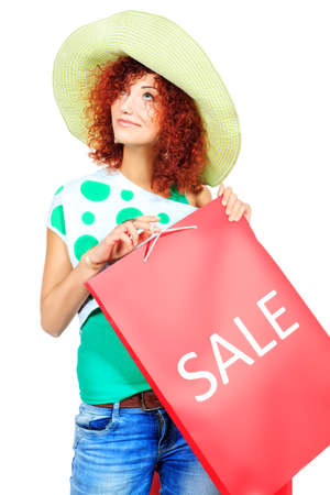 Happy young woman standing with shopping bags. Isolated over white. photo