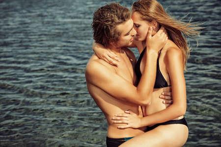 besos apasionados: Hermosa pareja de j?venes enamorados que tiene vacaciones en el mar.