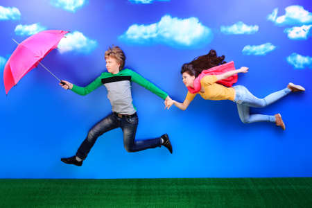 Couple of young people in love flying in the sky. Stock Photo