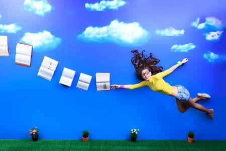 Feliz niña estudiante está volando en el cielo después de sus libros.