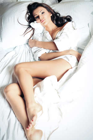 Happy beautiful young woman lying in a bed at home. photo
