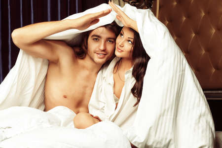 enamorados en la cama: La mujer joven y un hombre en el amor en una cama. Foto de archivo