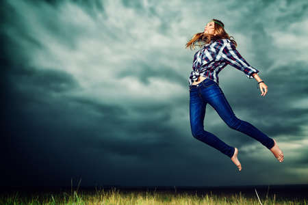Beautiful young woman jumping in the field over stormy evening sky. photo