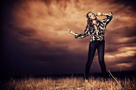 Romantic young woman in casual clothes standing in the field on a background of the storm sky.  photo