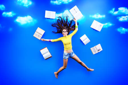 Happy girl student is flying in the sky after her books.  photo
