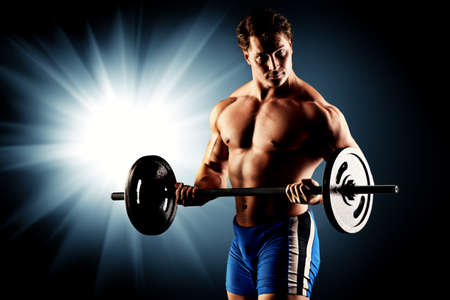 heavy lifting: Portrait of a handsome bodybuilder posing over black background. Stock Photo