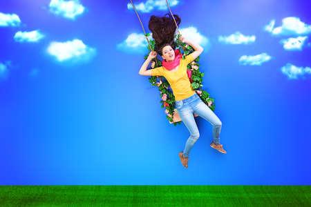 girl on swing: Pretty girl is swinging on a swing over blue sky.