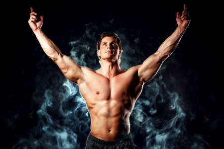 Portrait of a handsome muscular bodybuilder posing over black background. photo