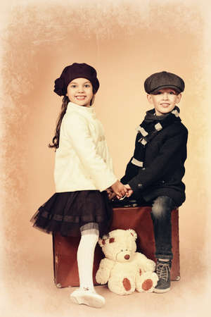 Cute little boy and girl are sitting on their old suitcases. Retro style. photo