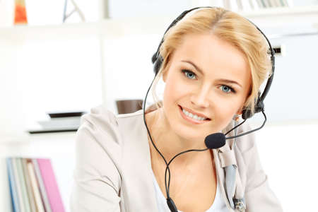 helpdesk: Portrait of smiling young woman operator in headset at office.