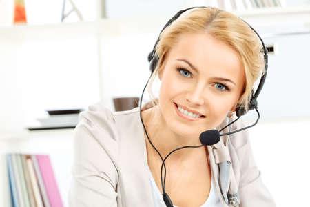 Retrato de la sonrisa joven operador de la mujer en el auricular en la oficina.