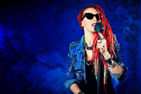Modern rock singer singing into a microphone. photo