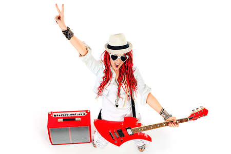 Modern girl rock musician is playing the electric guitar. Isolated over white. photo