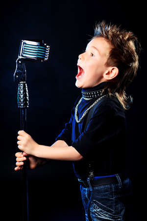 An emotional little boy is singing into a microphone like a rock musician.  photo
