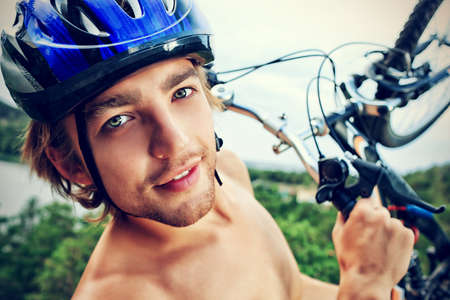 Young man cyclist holding his bicycle on the top of a hill. photo