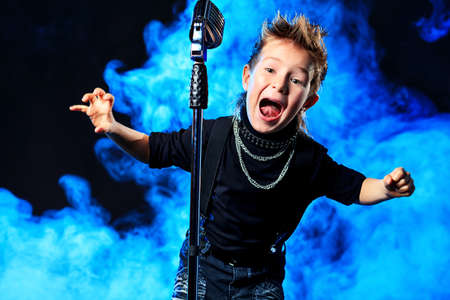 cool kids: An emotional little boy is singing into a microphone like a rock musician.