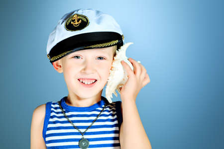 Little smiling sailor boy is listening to the sound of the sea in the shell. photo