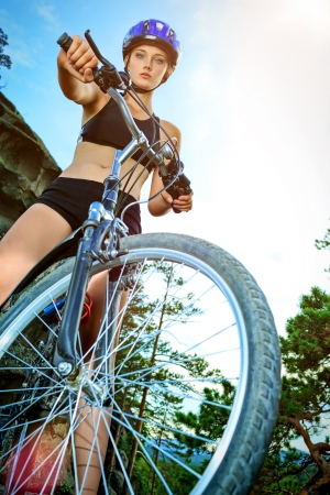 Active young woman rides a bike in the mountains. photo