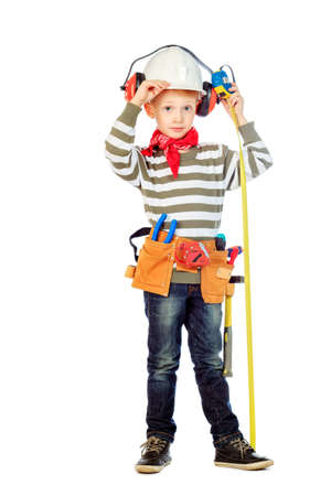 Little boy in a helmet plays in the builder with tools. isolated over white. photo