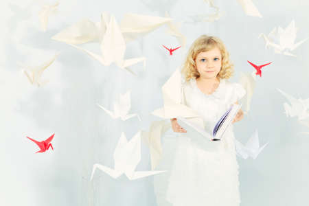 Beautiful little girl in her dream world surrounded with paper birds, reading fairytales. photo
