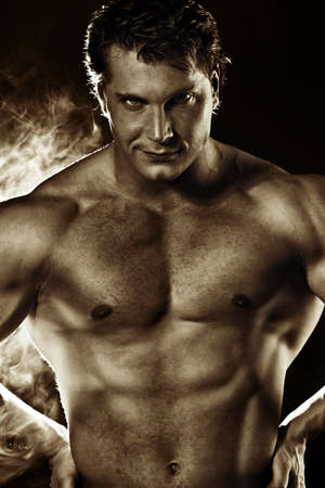 Portrait of a handsome muscular bodybuilder posing over dark background. Sepia. photo