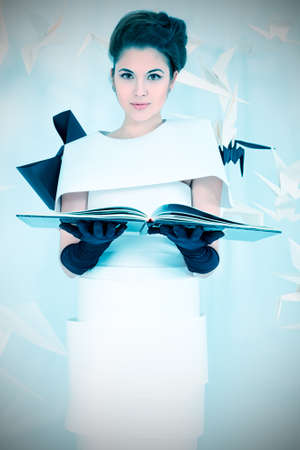 Art fashion photo of a gorgeous woman in paper dress reading a book. Black and white. photo