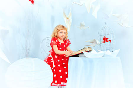 Beautiful little girl dreaming with her book and red paper bird in a birdcage. photo