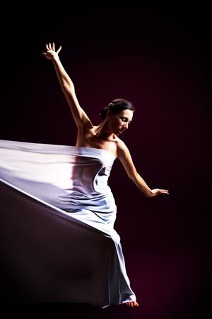 Art fashion photo of a beautiful woman dancing over black background. photo
